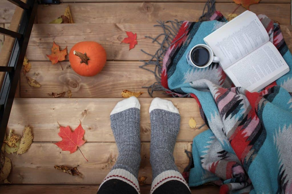 person wearing grey socks stands on wooden stairs with pumpkin, leaves, and coffee