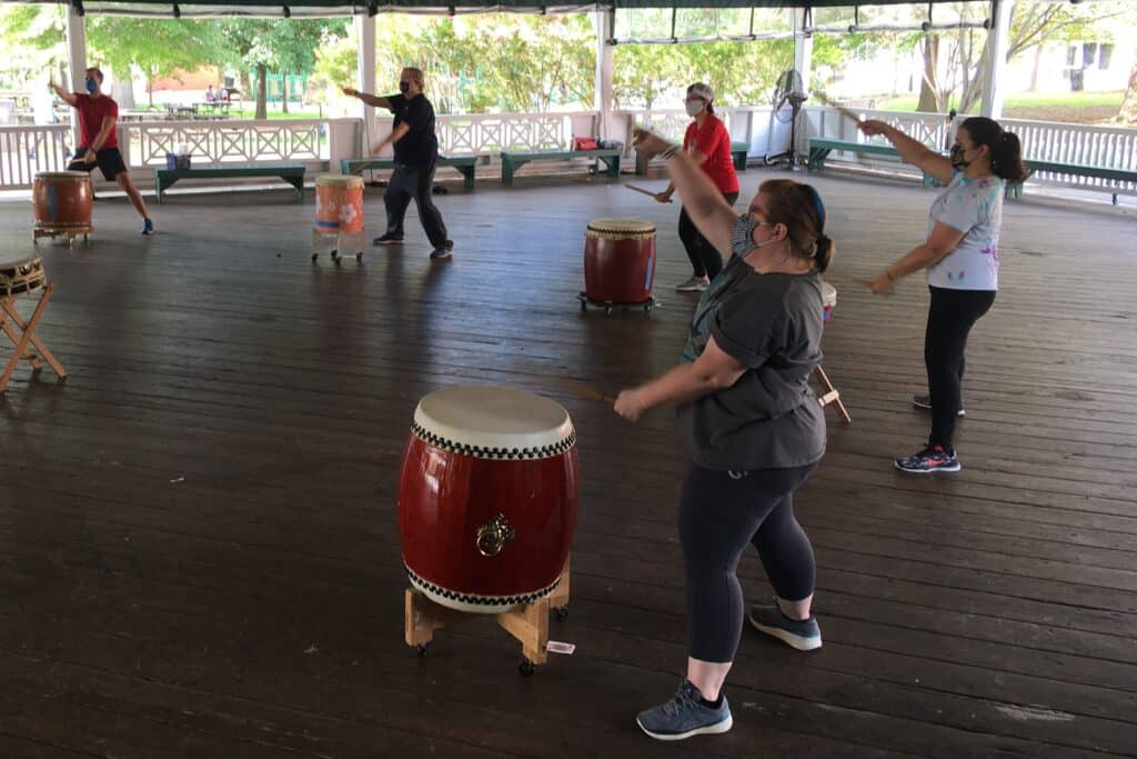 taiko players wearing masks practicing outdoors